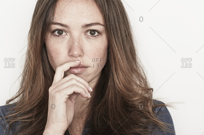 Close up of young woman with finger touching lip