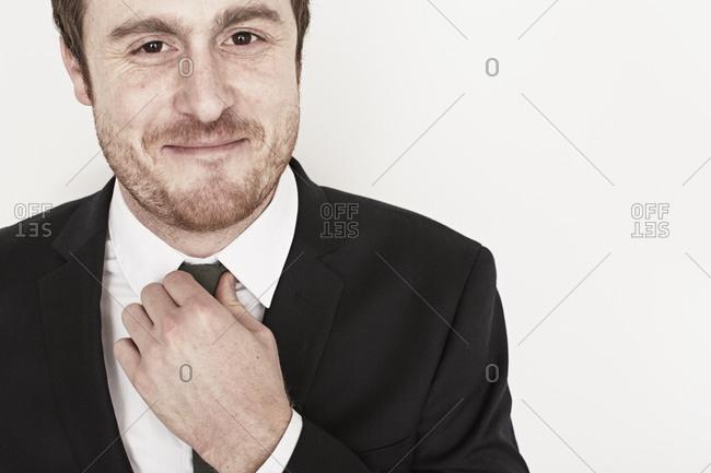 Man in suit adjusting tie