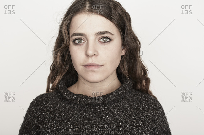 Portrait of a young female with wavy brown hair in a sweater