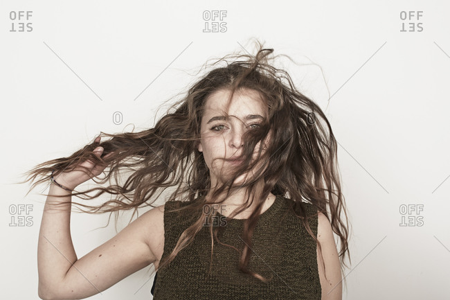 A young woman holding her disheveled hair