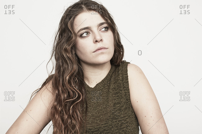 A pensive young woman with wavy brown hair