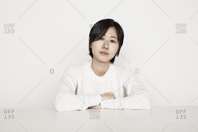 Young woman with arms folded on a table