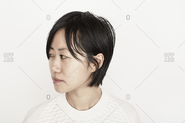 Young woman turning head in a white sweater