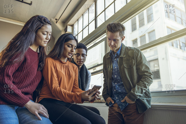 Group of people gathered around to look at a cell phone
