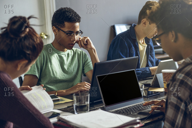 Group of young college students studying together