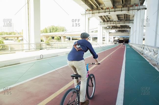 Rear view of male tourist cycling in cycle lane, Seoul, South Korea