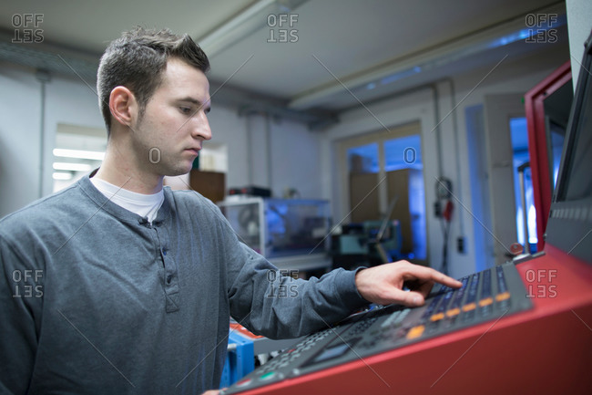 Young male technician using control panel for machine in workshop