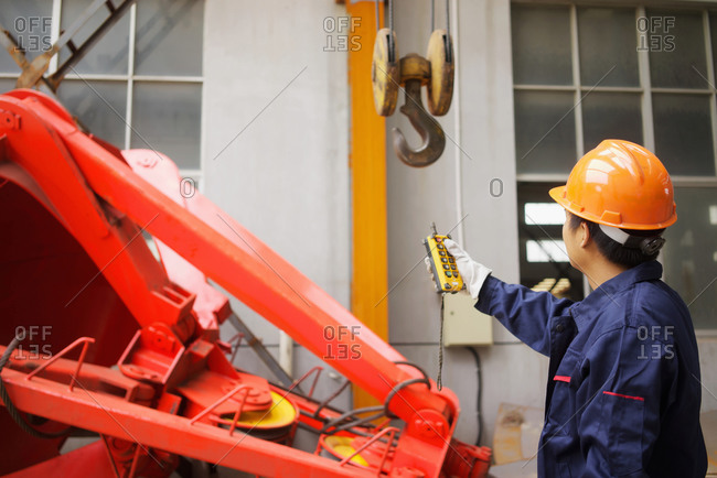 Worker using equipment in crane manufacturing facility, China