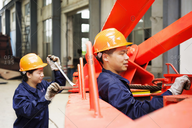 Workers using equipment in crane manufacturing facility, China