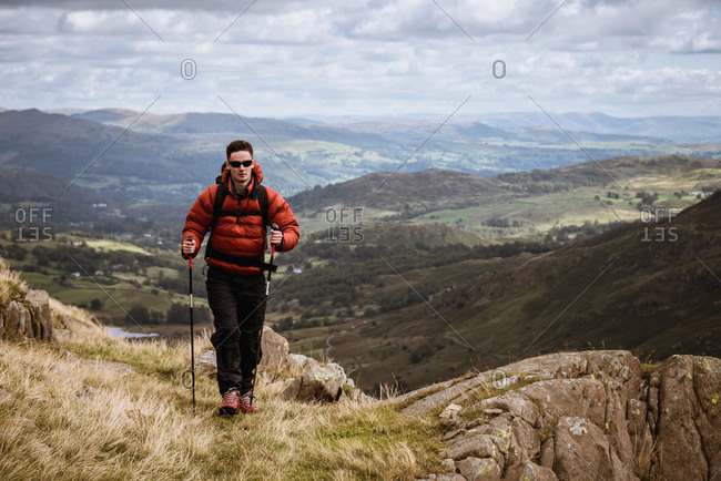 Young male hiker hiking up mountain, The Lake District, Cumbria, UK