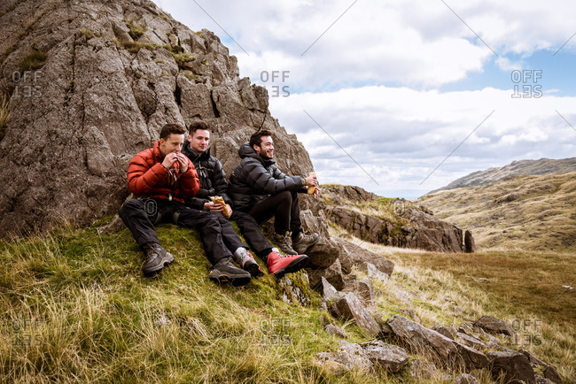 Three young male hiking friends eating sandwiches, The Lake District, Cumbria, UK