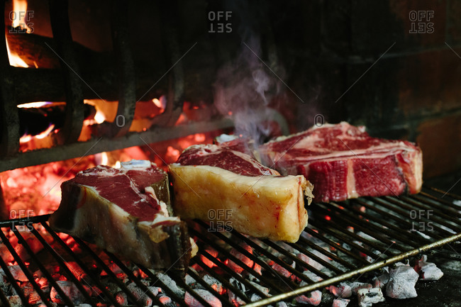Bistecca fiorentina (T bone steaks) grilling in front of open fire