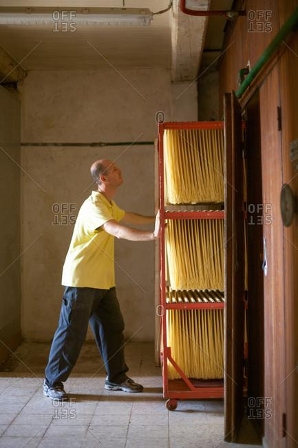 Male artisan pushing trolley of fresh spaghetti, Tuscany, Italy
