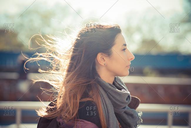 Mid adult woman walking along breezy roadside