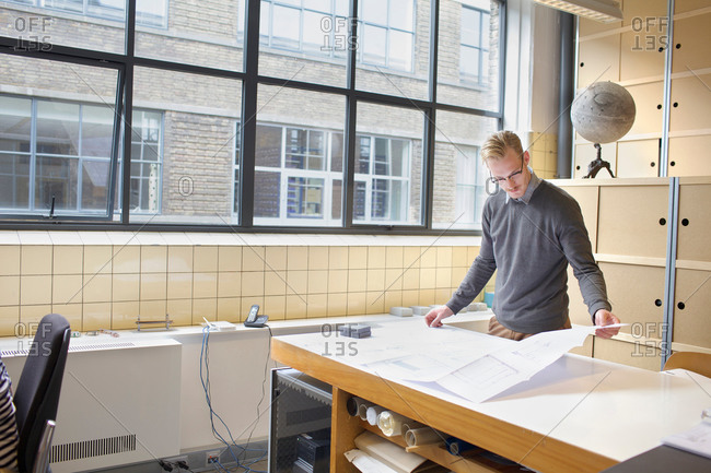 Male designer looking at blueprint in creative office