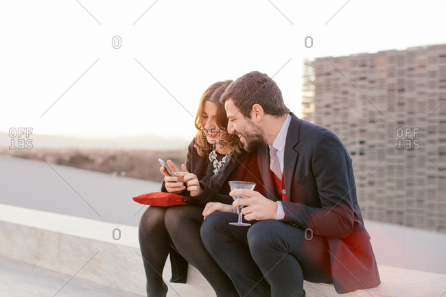 Two friends drinking together at party, woman showing man her mobile phone