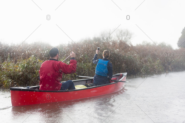 Woman taking a photo with her phone while canoeing with boyfriend