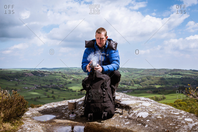 Male hiker with camping stove on top of Guise Cliff, Pateley Bridge, Nidderdale, Yorkshire Dales