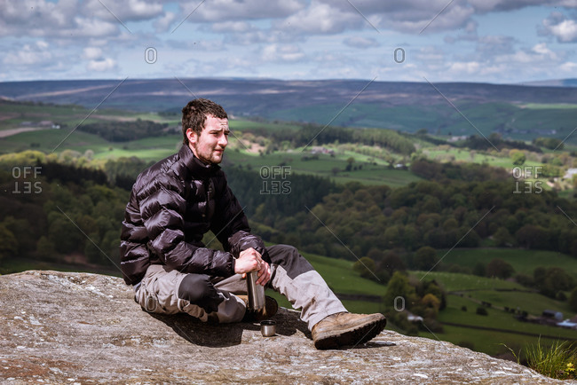 Young male hiker opening flask on top of Guise Cliff, Pateley Bridge, Nidderdale, Yorkshire Dales