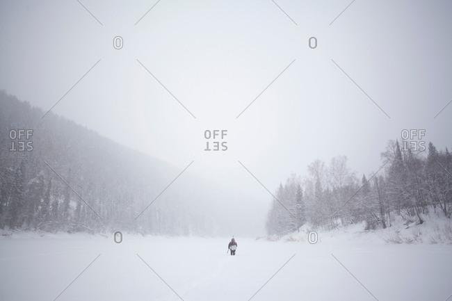 Rear view of man walking through snow covered valley, Sarsy Village, Sverdlovsk Oblast, Russia