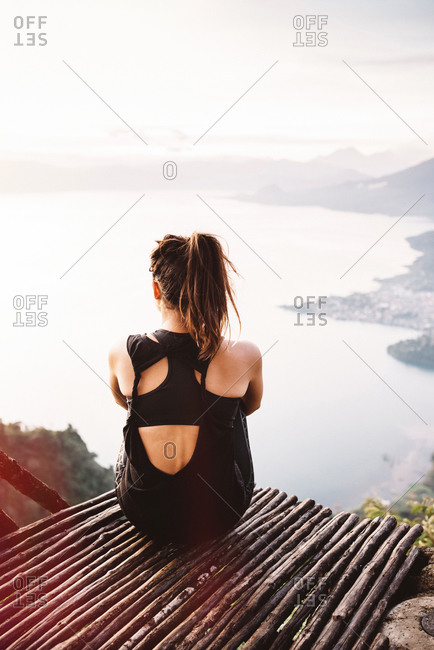 Rear view of young woman on balcony looking out over Lake Atitlan, Guatemala