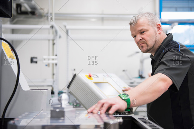 Factory worker using control panel at work station