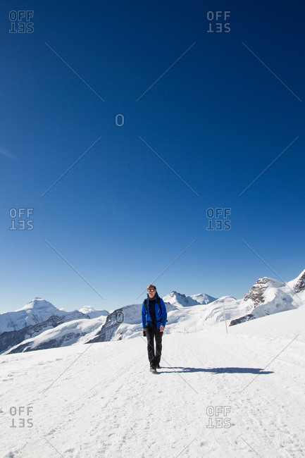 Male hiker hiking in snow covered landscape, Jungfrauchjoch, Grindelwald, Switzerland