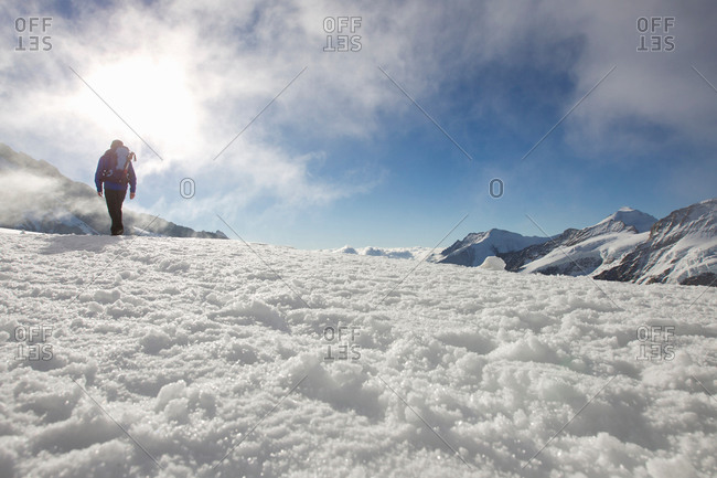 Low angle view of male hiker in snow covered landscape, Jungfrauchjoch, Grindelwald, Switzerland
