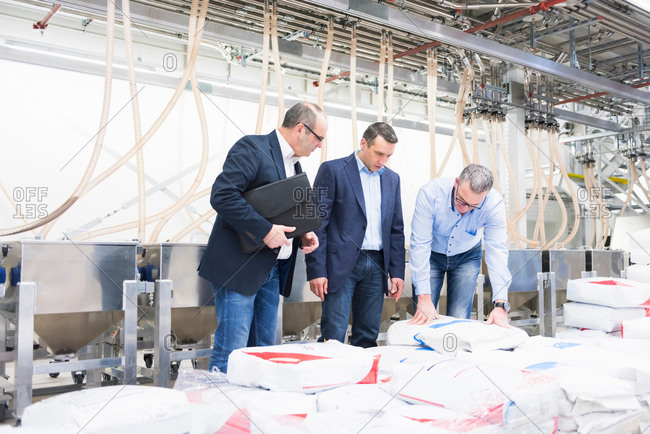 Businessmen and manager inspecting products in factory