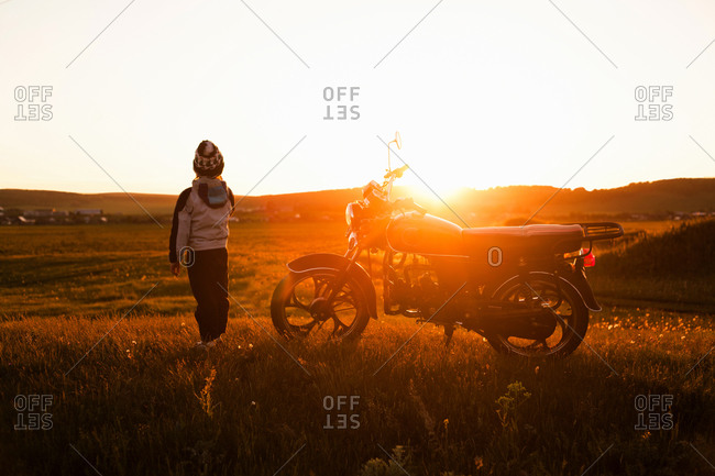 Rear view of boy and motorcycle at sunset, Sarsy village, Sverdlovsk Region, Russia
