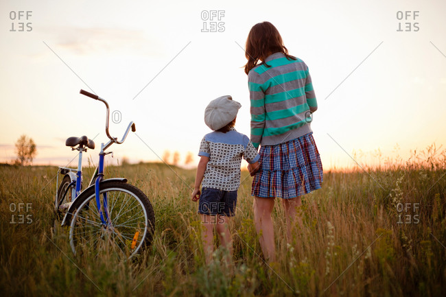 Rear view of boy and mother holding hands in field at sunset, Sarsy village, Sverdlovsk Region, Russia