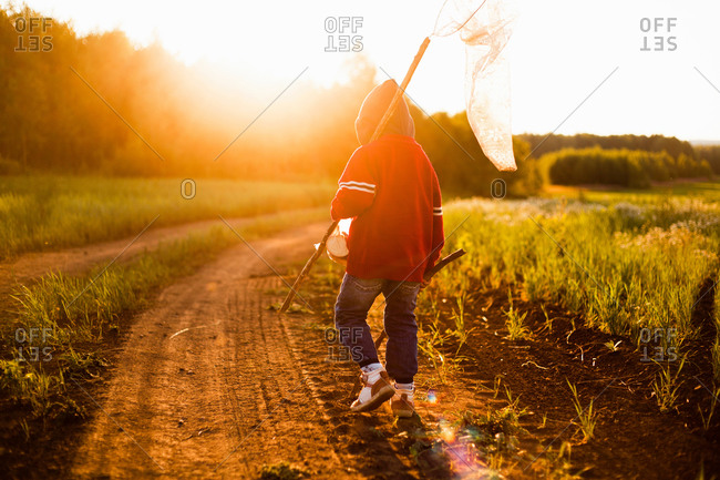 Rear view of boy with butterfly net walking along dirt track at sunset, Sarsy village, Sverdlovsk Region, Russia