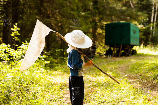 Boy in woods with butterfly net, Sarsy village, Sverdlovsk Region, Russia