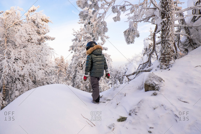 Boy walking in snow covered mountain forest, Nizhniy Tagil, Sverdlovsk Region, Russia