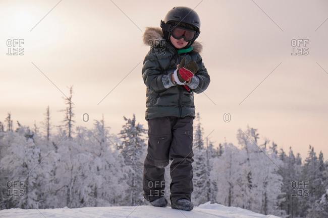 Boy putting on glove in snow covered forest, Nizhniy Tagil, Sverdlovsk Region, Russia