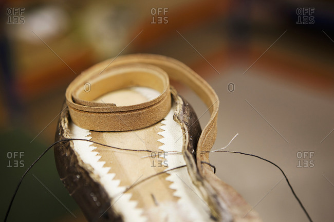 Close up of thread and shoe leather in shoe makers workshop