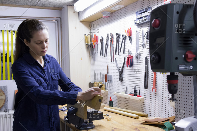 Young female carpenter planing timber in workshop vice