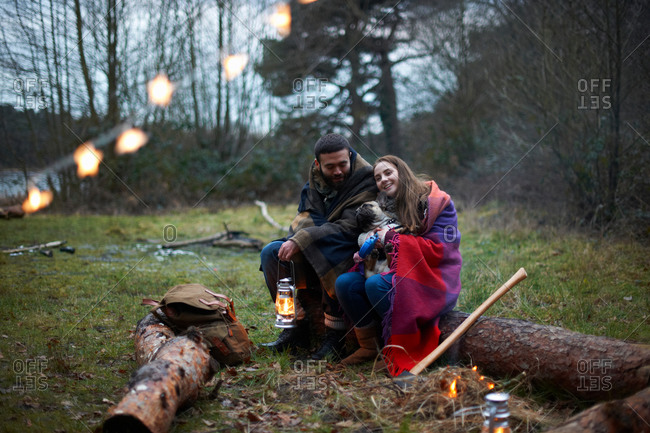 Young camping couple with dog wrapped in blanket in woods