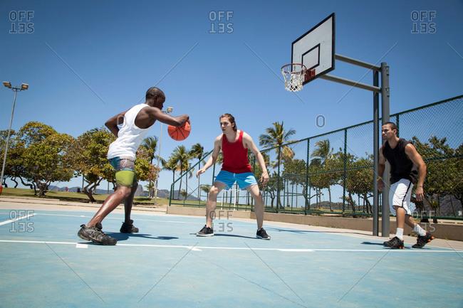 Three men practicing basketball on basketball court