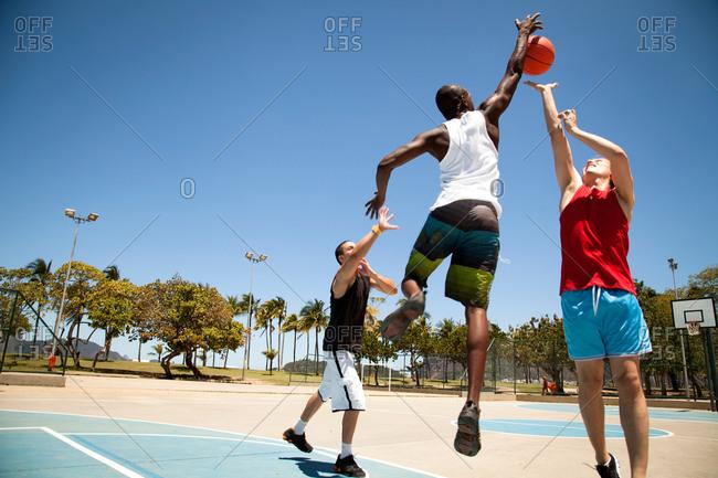 Three man basketball team practicing on basketball court