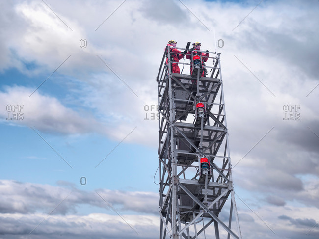 Two tower workers on offshore radio tower on windfarm, low angle view