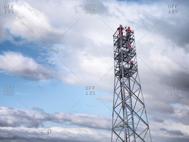 Tower workers on offshore radio tower on windfarm, low angle view