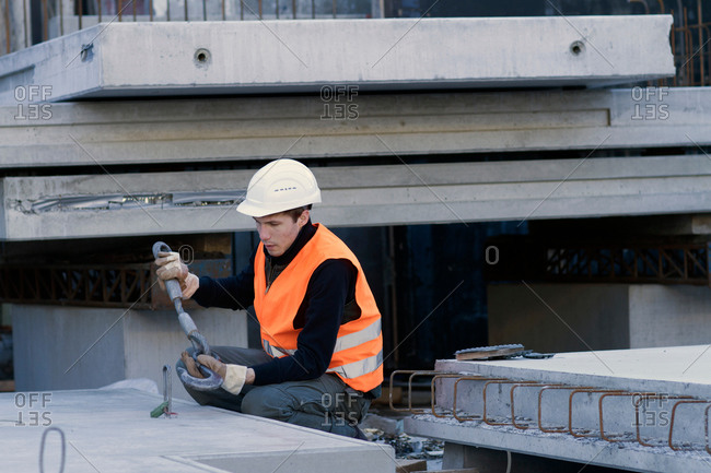 Factory worker attaching hook to concrete block in concrete reinforcement factory