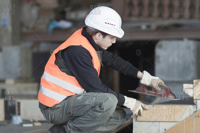 Factory worker using finishing trowel on concrete in concrete reinforcement factory