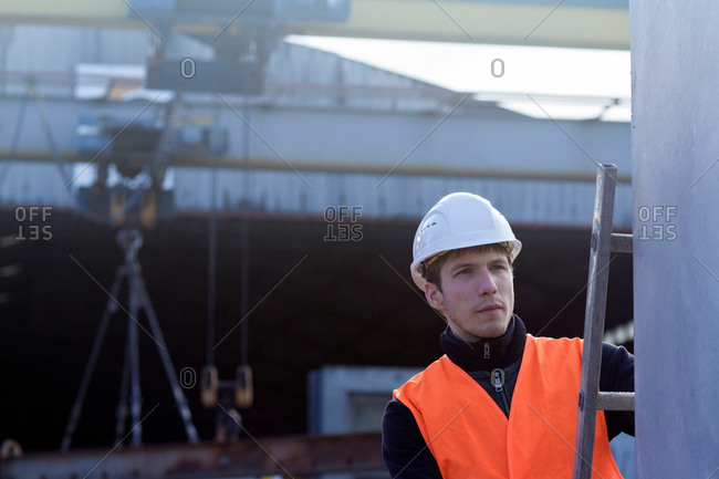 Factory worker on ladder checking concrete block in concrete reinforcement factory
