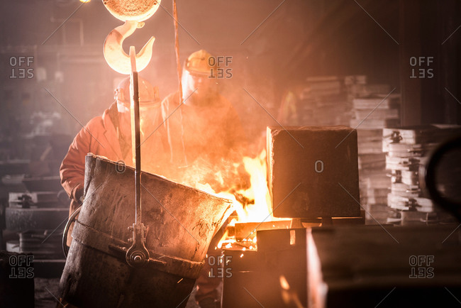 Workers pouring molten metal into moulds from flask in foundry