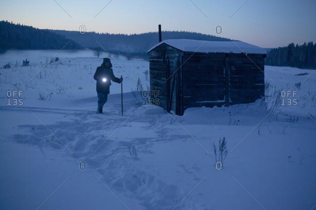 Man in snow covered landscape pointing torch at dusk, Sarsy village, Sverdlovsk Oblast, Russia