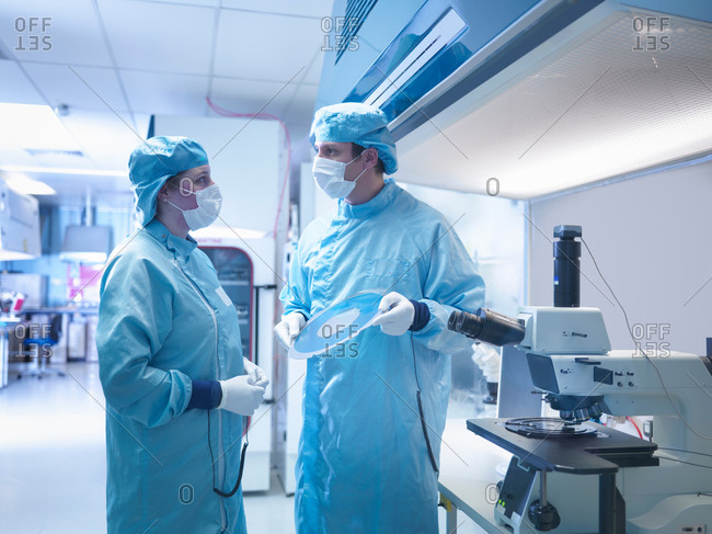 Electronics worker in clean room with silicon wafer