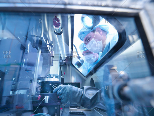 Electronics workers looking into sealed work station window in clean room laboratory
