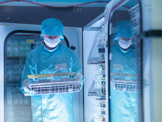 Worker checking archived electronic components in nitrogen atmosphere in clean room laboratory